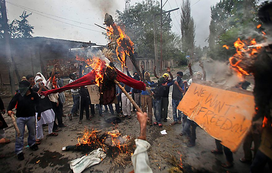 Kashmiri protesters shout slogans as they burn effigies of Indian prime minister and the Jammu and Kashmir state chief minister in Srinagar, India, Tuesday, Sept. 14, 2010. Indian police patrolled the streets of Kashmir on Tuesday, threatening to shoot anyone defying a rigid curfew imposed on the region a day after troops battled protesters in the streets in violence that killed 19 people. (AP Photo/Altaf Qadri)