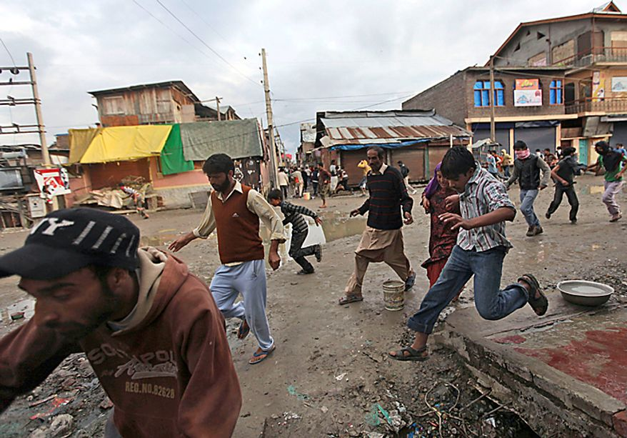 Kashmiri Muslim protesters run for cover as Indian paramilitary soldiers fire live ammunition during a protest in Srinagar, India, Tuesday, Sept. 14, 2010. Indian police patrolled the streets of Kashmir on Tuesday, threatening to shoot anyone defying a rigid curfew in the disputed region a day after 19 people died in battles between troops and protesters. (AP Photo/Dar Yasin)