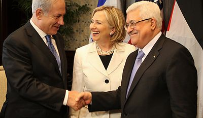 """In this photo released by the Palestinian President Office, Israeli Prime Minister Benjamin Netanyahu (left) shakes hands with Palestinian President Mahmoud Abbas (second right), joined by U.S. Secretary of State Hillary Rodham Clinton during bilateral talks Tuesday at the Red Sea resort of Sharm el-Sheikh, Egypt. Convening a new round of negotiations Tuesday between Israel and the Palestinians, U.S. Secretary of State Hillary Rodham Clinton said the """"time is ripe"""" for a Mideast peace. (Associated Press)"""