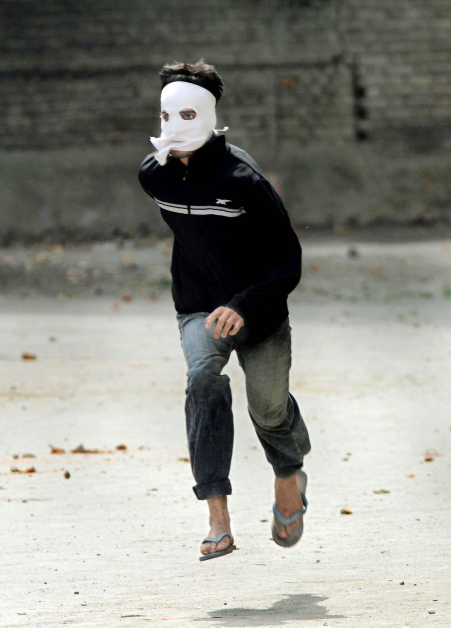 A Kashmiri Muslim protester runs for cover as Indian paramilitary soldiers pursue him near Srinagar, India, on Wednesday. (Associated Press)