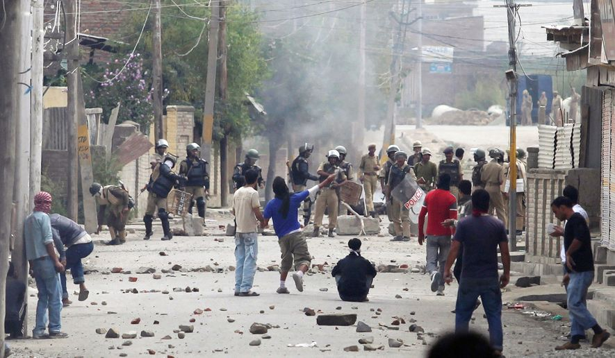 Kashmiri protesters hurl stones at government forces during a clash on the outskirts of Srinagar, India, on Wednesday. Leaders of India's main political parties searched for a strategy to end months of increasingly violent protests in the region. (Associated Press)