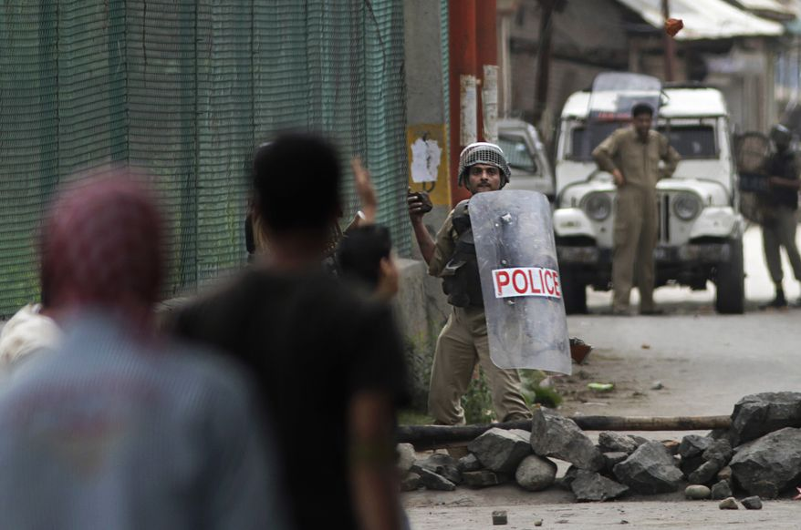 An Indian paramilitary soldier prepares to throw a stone at Kashmiri Muslim protesters during a protest in the outskirts of Srinagar, India, on Wednesday, Sept.15, 2010. Leaders of India's main political parties debated Wednesday whether to ease harsh security laws in Indian-controlled Kashmir as the government searched for a strategy to end months of increasingly violent protests in the region. (AP Photo/Dar Yasin)