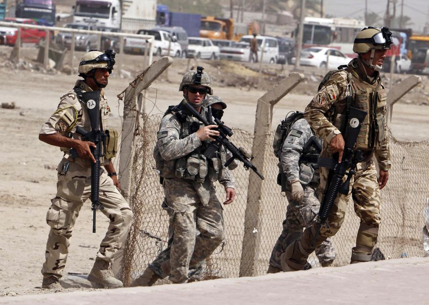 **FILE** U.S. Army soldiers and Iraqi security forces secure the scene of a roadside bomb attack in Basra, Iraq, in September. (Associated Press)