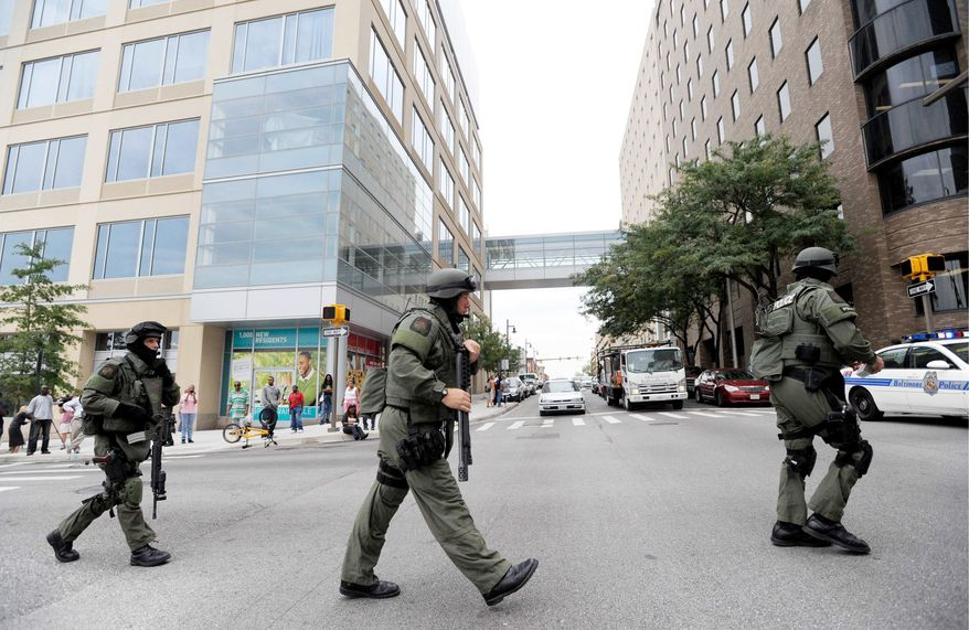 ASSOCIATED PRESS Members of a Baltimore County SWAT team take up positions at Johns Hopkins Hospital in Baltimore on Thursday after a man shoots a doctor during a consultation. The surgeon survived but the gunman killed his ailing mother and himself in a hospital room before the standoff of more than two hours ended.