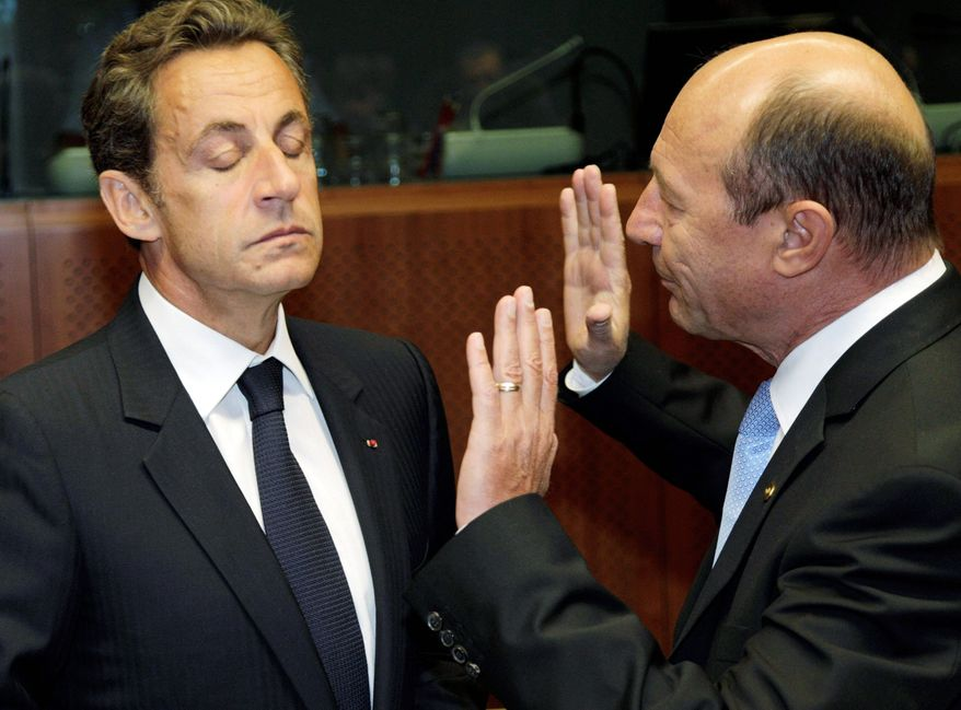 ASSOCIATED PRESS French President Nicolas Sarkozy (left) speaks with Romanian President Traian Basescu during a roundtable meeting at an EU summit in Brussels on Thursday. A summit of government leaders seeking to mold a united European Union front on the global stage opened in disarray over France's expulsion of Gypsies and comparisons with World War II deportations.