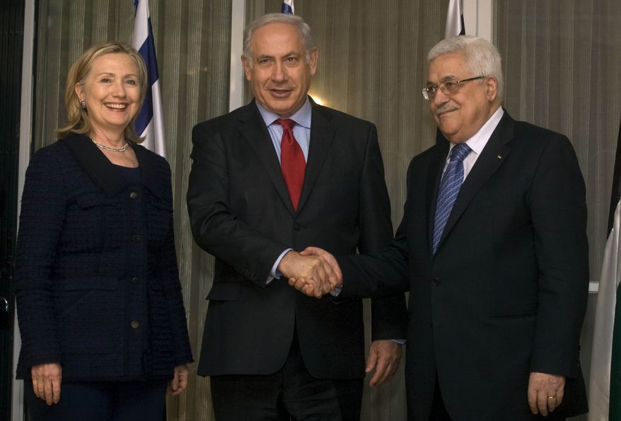Israeli Prime Minister Benjamin Netanyahu (center) shakes hands with Palestinian President Mahmoud Abbas as U.S. Secretary of State Hillary Rodham Clinton smiles during a meeting at the prime minister's residence in Jerusalem on Wednesday, Sept. 15, 2010. (AP Photo/Lior Mizrahi, Pool)