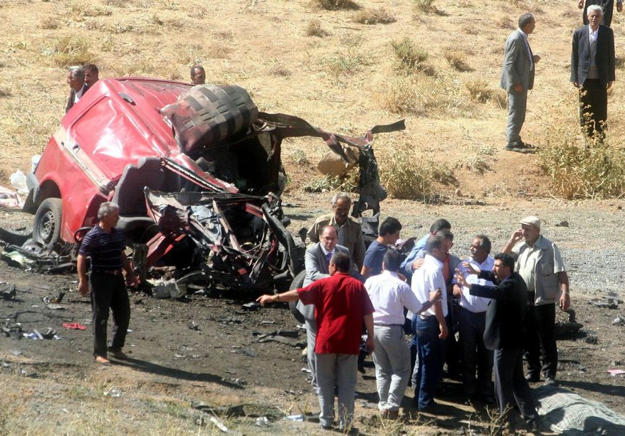 People seen at the explosion site after a roadside bomb attack killed nine people traveling aboard a minibus near the village of Gecitli in the rugged Hakkari province bordering Iran and Iraq, Turkey, Thursday, Sept. 16, 2010, in the latest violence to shake. (AP Photo/Yilmaz Kazandioglu, Anatolia Agency)