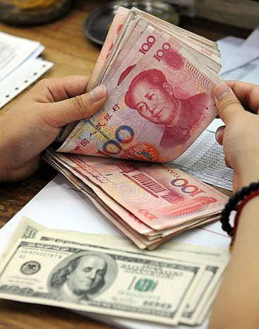 A clerk counts Chinese yuan banknotes at a bank in Hefei, in central China's Anhui province, on Wednesday, Sept. 15, 2010. (AP Photo)