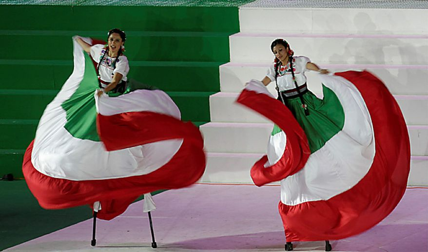 Women wearing dresses in the colors of Mexico's flag dance on stilts during bicentennial celebrations at the Zocalo plaza in Mexico City, Wednesday Sept. 15, 2010. Mexico celebrates the 200th anniversary of its 1810 independence uprising. (AP Photo/Marco Ugarte)