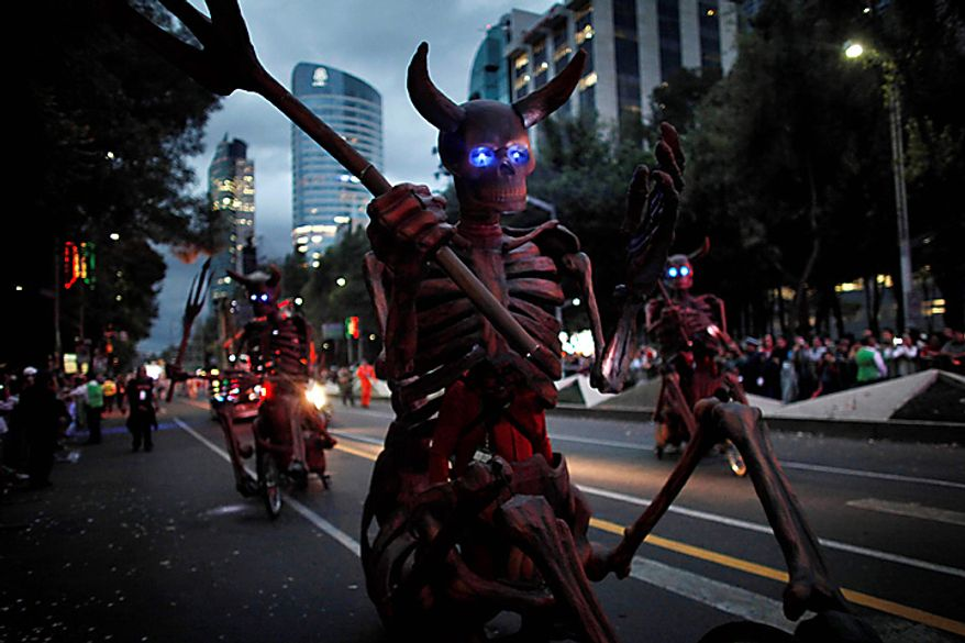 People dressed as horned skeletons cycle during the bicentennial parade in Mexico City, Wednesday Sept. 15, 2010. Mexico celebrates the 200th anniversary of its 1810 independence uprising. (AP Photo/Miguel Tovar)