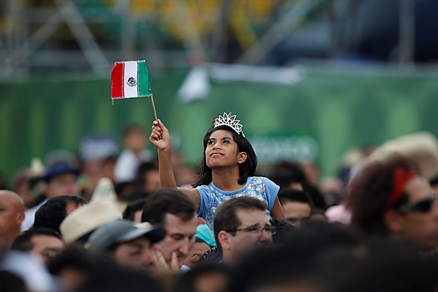 A person waves a Mexican flag during bicentennial celebrations at the Zocalo plaza in Mexico City, Wednesday Sept. 15, 2010. Mexico celebrates the 200th anniversary of its 1810 independence uprising. (AP Photo/Alexandre Meneghini)