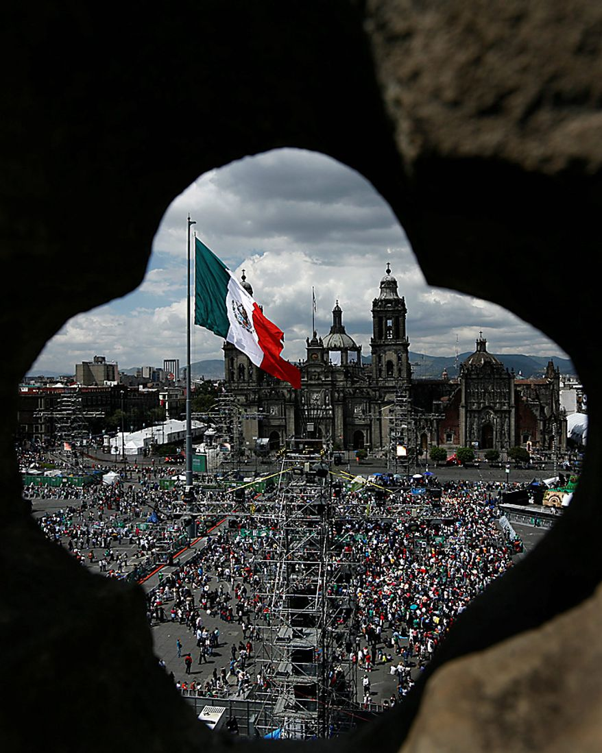 People begin to gather in Mexico City's downtown Zocalo plaza for bicentennial celebrations, Wednesday Sept. 15, 2010.  Mexico celebrates the 200th anniversary of its 1810 independence uprising. (AP Photo/Marco Ugarte)