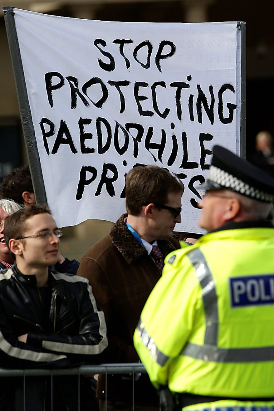 A British police officer stands by as protestors hold a banner during the visit of Pope Benedict XVI to Edinburgh, Scotland, Thursday Sept. 16, 2010.  Pope Benedict XVI arrives in the United Kingdom on Thursday for a four-day visit, a controversial yet historic state trip that has been overshadowed by the sex abuse scandals which have shaken confidence in the Roman Catholic Church.(AP Photo/Jon Super).
