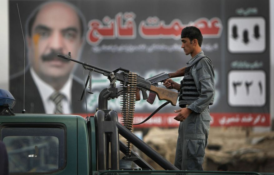 An Afghan policeman provides a very visible show of security in front of an election campaign billboard in Kabul, Afghanistan, Friday, Sept. 17, 2010. Afghan President Hamid Karzai urged Afghans to vote in this weekend's parliamentary election despite threats from the Taliban warning people not to leave their homes. (AP Photo/ Gemunu Amarasinghe)