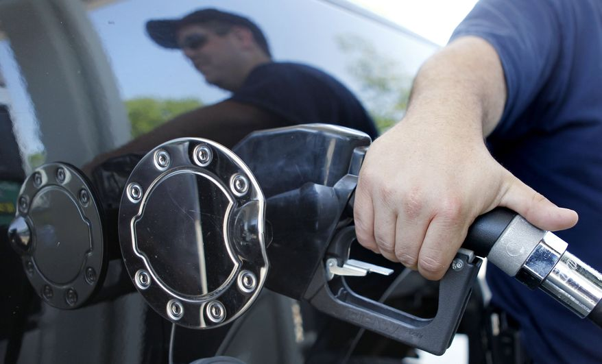 **FILE** In this May 26 photo, Kevin Stearns of Oxford, Mass., fills up his pick up truck at a gas station in Milford, Mass. (Associated Press)