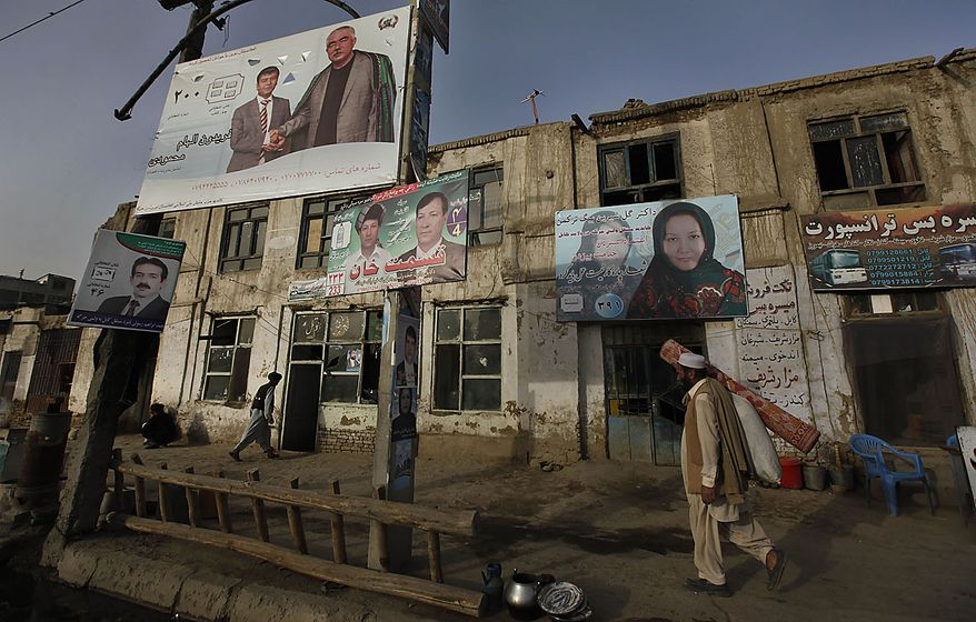 An Afghan man, carrying a floor mat, walks past election campaign billboards in Kabul, Afghanistan, Friday, Sept. 17, 2010. Police set up extra checkpoints across Afghanistan on Friday to scan for suicide bombers and insurgents a day ahead of parliamentary polling. (AP Photo/Gemunu Amarasinghe)