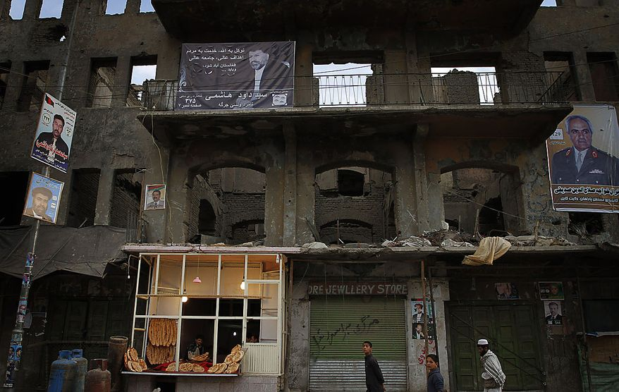 Election posters of Afghan parliamentarian candidates pasted on a partly demolished building in Kabul, Afghanistan, Friday, Sept. 17, 2010. Afghanistan will go to parliamentary election on Sept. 18 as the Taliban have warned of countrywide attacks on Saturday targeting voters and election workers. (AP Photo/Musadeq Sadeq)