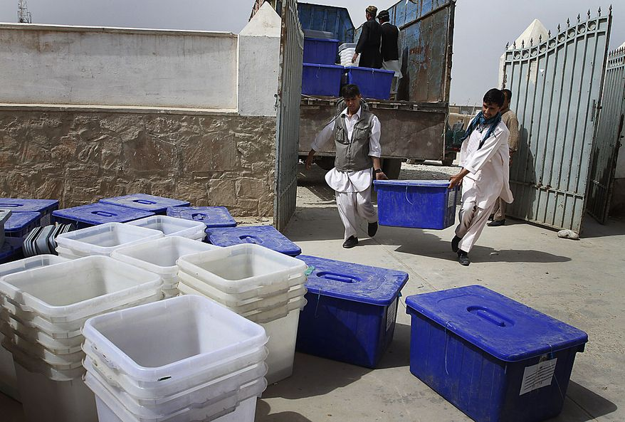 Afghan election workers carry a ballot box into a polling station on the eve of the parliamentary election in Kabul, Afghanistan, Friday, Sept. 17, 2010. Afghanistan will go to parliamentary election on Saturday as the Taliban have warned of countrywide attacks targeting voters and election workers. (AP Photo/Musadeq Sadeq)