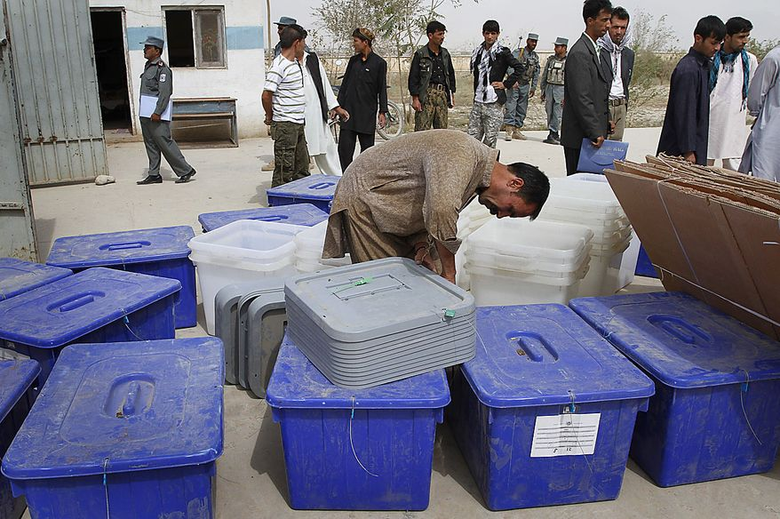 An Afghan election worker counts distributed ballot materials at a polling station on the eve of the parliamentary election in Kabul, Afghanistan, Friday, Sept. 17, May. 2010. Afghanistan will go to parliamentary election Saturday as the Taliban have warned of countrywide attacks targeting voters and election workers. (AP Photo/Musadeq Sadeq)