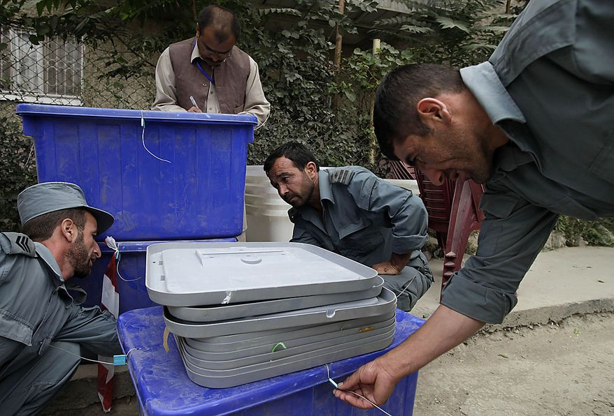Police officers and poll workers check the seals on poll materials as they are delivered to a polling center in Kabul, Afghanistan, Friday, Sept. 17, 2010. Afghanistan will elect the lower house of its parliament on Saturday. (AP Photo/Saurabh Das)
