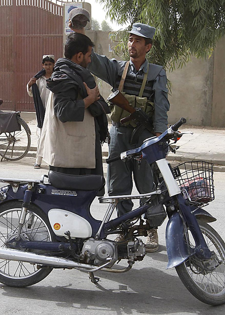 A police officer frisks a motorcyclist at a check point in Kandahar, Afghanistan, Friday, Sept. 17, 2010.  Afghan President Hamid Karzai urged citizens to vote in Saturday's parliamentary election despite fears of violence and threats from the Taliban warning people not to leave their homes. (AP Photo/Allauddin Khan)