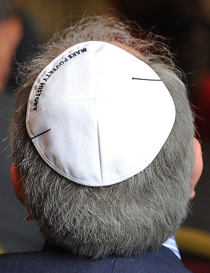 """A member of the audience wears a Yarmulke with the message """"Make Poverty History"""" embroidered on it as he watches as Pope Benedict XVI attends a meeting of religious leaders at St Mary's University College Chapel at Twickenham in west London, Friday, Sept. 17, 2010. The Pope is on a four-day visit to England and Scotland. (AP Photo/Toby Melville, Pool)"""