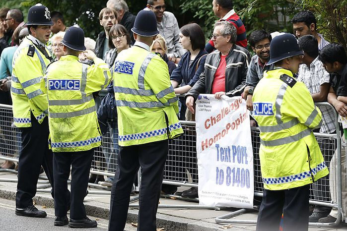 Line of police officers watch over the crowd outside St Mary's University College in Twickemham, London where Pope Benedict XVI is attending a celebration of catholic education, Friday, Sept. 17, 2010. Pope Benedict XVI  is on a four-day visit, the first-ever state visit by a Pope to Britain. (AP Photo/Sang Tan)