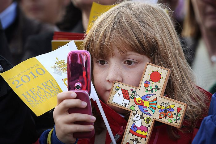 A school-girl takes a photograph of Pope Benedict XVI  with her phone at at St Mary's University College during day two of the Pope's four day state visit to Britain in Twickenham, London Friday Sept.17, 2010. (AP Photo/Peter Macdiarmid, Pool)