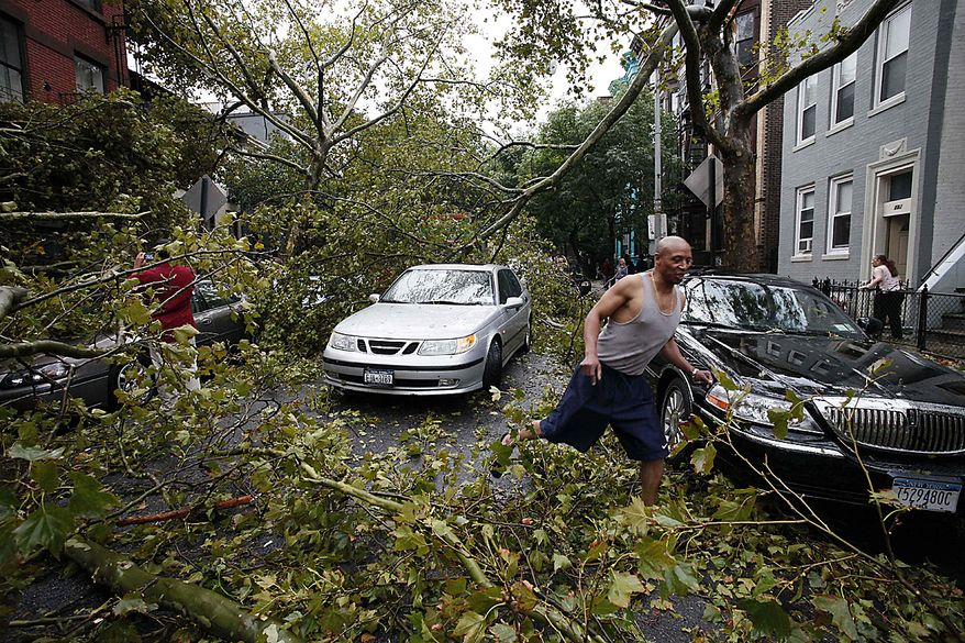 A man steps through fallen branches in the Park Slope neighborhood in the Brooklyn borough of New York, Thursday, Sept. 16, 2010. A brief but severe storm has swept through New York City, uprooting trees and damaging cars. (AP Photo/Mark Lennihan)