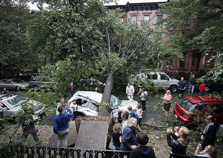 Residents in the Park Slope neighborhood in the Brooklyn borough of New York circle around a car crushed by a fallen tree, Thursday, Sept. 16, 2010. A brief but severe storm has swept through New York City, uprooting trees and damaging cars. (AP Photo/Mark Lennihan)