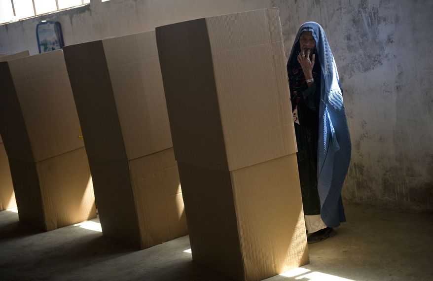 An Afghan woman reacts before casting her ballot in parliamentary elections at a polling station in Kabul, Afghanistan, on Saturday Sept. 18, 2010. (AP Photo/Hossein Fatemi)