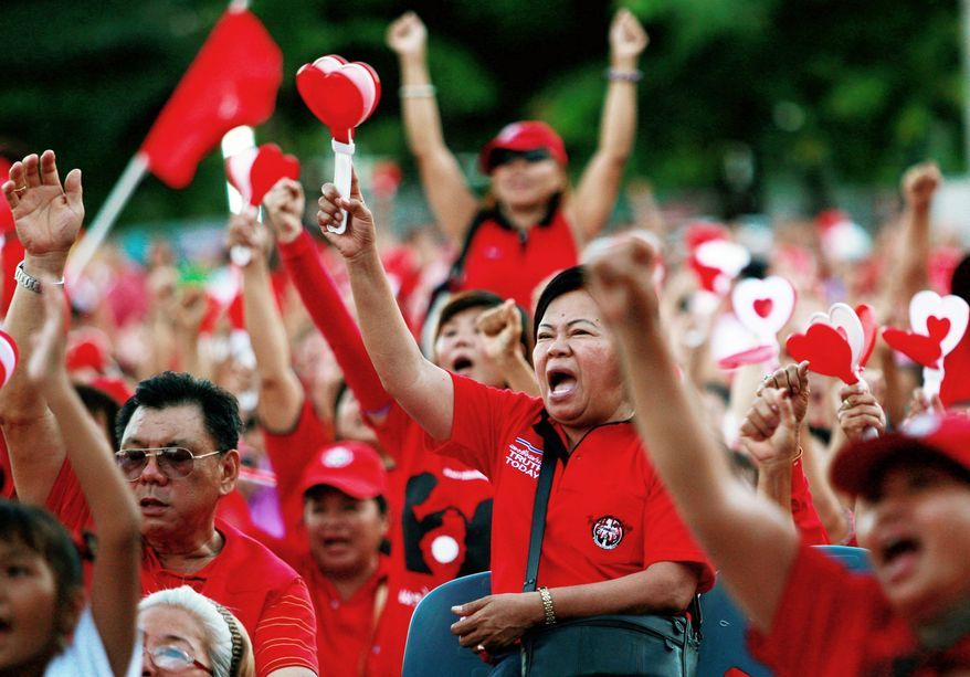 ASSOCIATED PRESS Red Shirt protesters against the government cheer Sunday during a rally in Chiang Mai province, northern Thailand. Thousands of the demonstrators, who are supporters of deposed Prime Minister Thaksin Shinawatra, took part in a rally marking the fourth anniversary of the military coup that ousted Mr. Thaksin from power. Chiang Mai is his hometown.