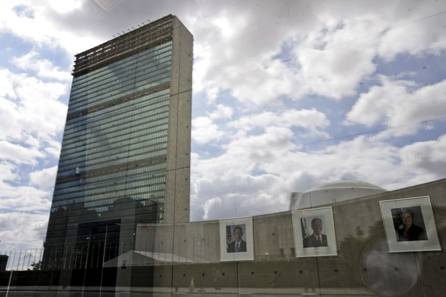 **FILE** The United Nations building is reflected on the window of the U.S. mission to the U.N. as portraits of President Obama (left), Vice President Joseph R. Biden, and then-Secretary of State Hillary Clinton hang in the lobby on Sept. 18, 2010, in New York. (Associated Press)
