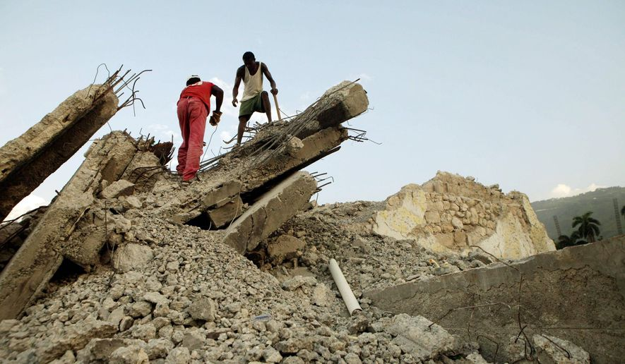 Two men remove rubble in late August from a building destroyed by the Jan. 12 earthquake in Port-au-Prince. Most Haitians just live and work around the piles of debris. (Associated Press)