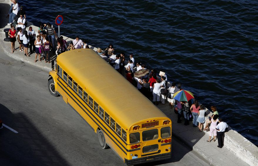 Government employees line up to enter a state-run bus after work in Old Havana, Cuba, Monday Sept. 13, 2010. Raul Castro's government announced it will cast off at least half a million state employees by mid-2011 and reduce restrictions on private enterprise to help them find new jobs. (AP Photo/Javier Galeano)