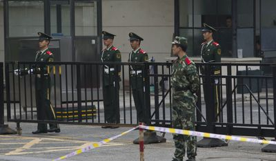 Paramilitary police and plainclothes police officers, background, guard the gate of Japanese Embassy in Beijing on Sept. 20, 2010. China broke off high-level government contacts with Japan over the extended detention of a fishing boat captain arrested near disputed islands. (Associated Press)