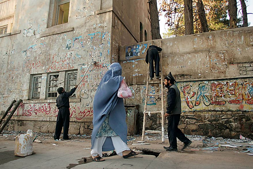 Policemen clean a wall of posters of candidates who contested in the parliamentary elections, in Herat, Afghanistan, Monday Sept. 20, 2010. Afghan election observers urged President Hamid Karzai's government on Monday to allow an independent investigation into reports of widespread fraud during last weekend's parliamentary elections, including intimidation of voters and interference by powerful warlords. (AP Photo/Reza Shirmohammadi)