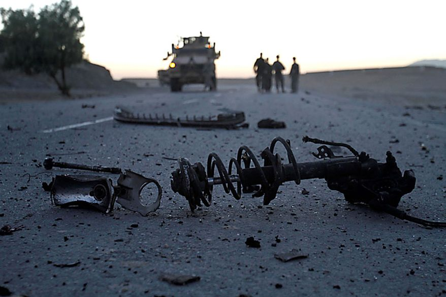 U.S soldiers inspect a site after a suicide car-bomb exploded in Behsood district of Jalalabad, Afghanistan, Monday Sept. 20, 2010. The attack on a NATO convoy reportedly injured four Afghan civilians. (AP Photo/Rahmat Gul)