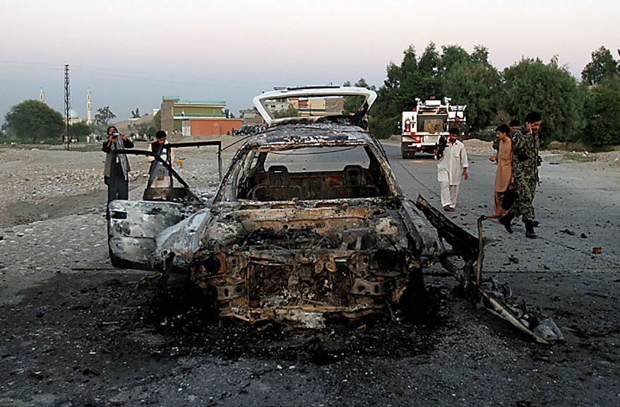 An Afghan soldier and locals walk by a site after a suicide car-bomb exploded in Behsood district of Jalalabad, Afghanistan, Monday Sept. 20, 2010. The attack on a NATO convoy reportedly injured four Afghan civilians. (AP Photo/Rahmat Gul)