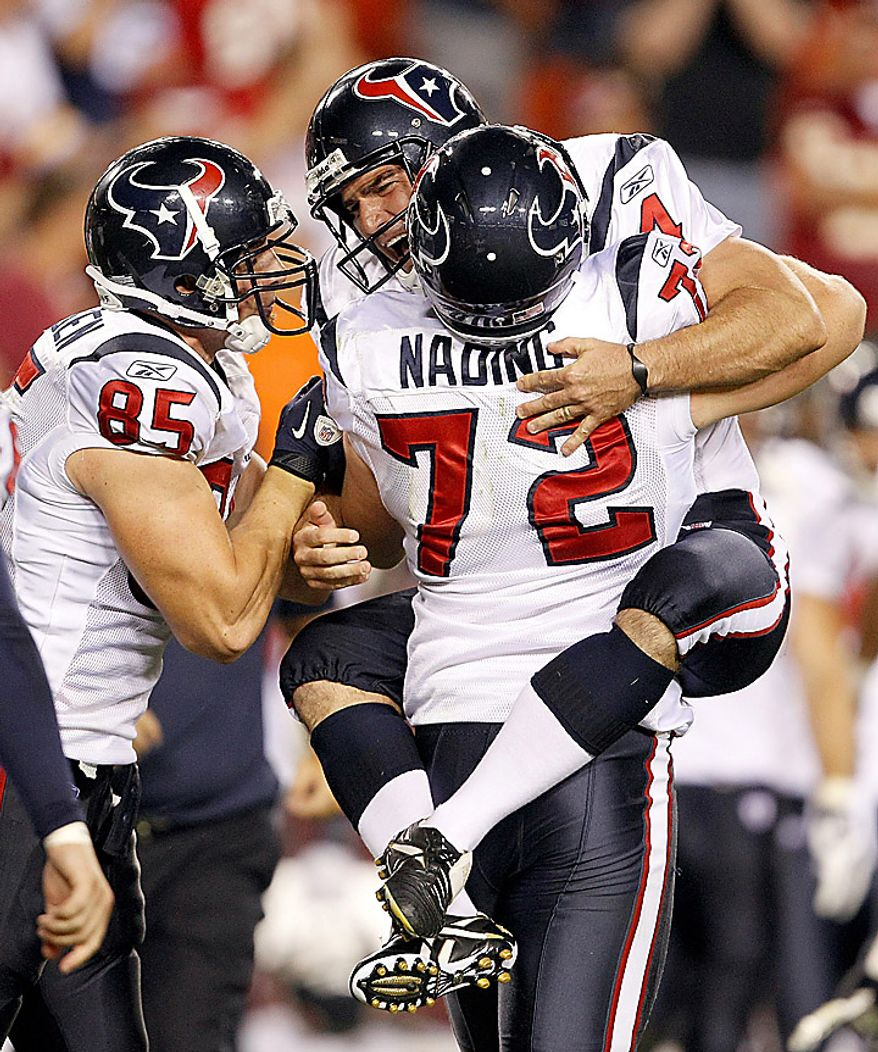 Houston Texans' Neil Rackers, right rear, is congratulated by defensive end Jesse Nading (72) and tight end Joel Dreessen (85) after kicking a field goal during overtime in an NFL football game against the Washington Redskins in Landover, Md., on Sunday, Sept. 19, 2010. The Texans won 30-27. (AP Photo/Evan Vucci)