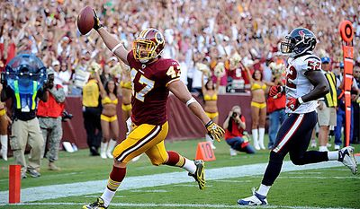 Washington Redskins tight end Chris Cooley scores a touchdown as Houston Texans linebacker Xavier Adibi watches during the second half an NFL football game in Landover, Md., on Sunday, Sept. 19, 2010.  (AP Photo/Nick Wass)