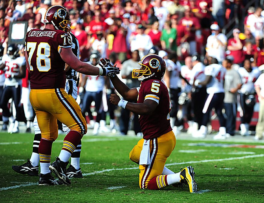 Washington Redskins quarterback Donovan McNabb is helped up by teammates Kory Lichtensteiger during the second quarter against the Houston Texans at FedEx Field in Washington on September 19, 2010.   UPI/Kevin Dietsch