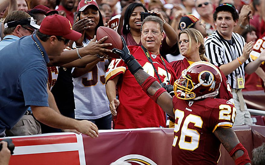 Washington Redskins running back Clinton Portis gives the ball to the fans after scoring during the first half of an NFL football game against the Houston Texans in Landover, Md., on Sunday, Sept. 19, 2010.  (AP Photo/Evan Vucci)