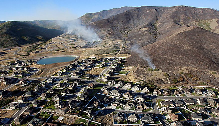 Small fires continue to burn near homes in Herriman, Utah on Monday, Sept. 20, 2010. A wind-stoked wildfire sparked at a firing range during a National Guard training session blazed across thousands of acres Monday as crews rushed to keep it from burning more than four homes that were destroyed overnight. The fire moved back on itself Monday as the Utah National Guard acknowledged it wasn't the first time that live-fire exercises had sparked a fire at Camp Williams, a sprawling compound 30 miles south of Salt Lake City. (AP Photo/Scott G Winterton, Pool)