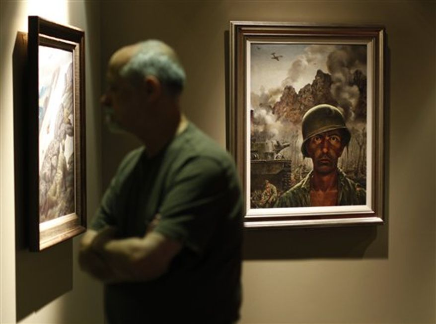In this Sept. 15, 2010 photo, a person passes images in the Art of the American Soldier exhibit prior to its opening, at the National Constitution Center, in Philadelphia.  The exhibition is scheduled to open Sept. 24. (AP Photo/Matt Rourke)