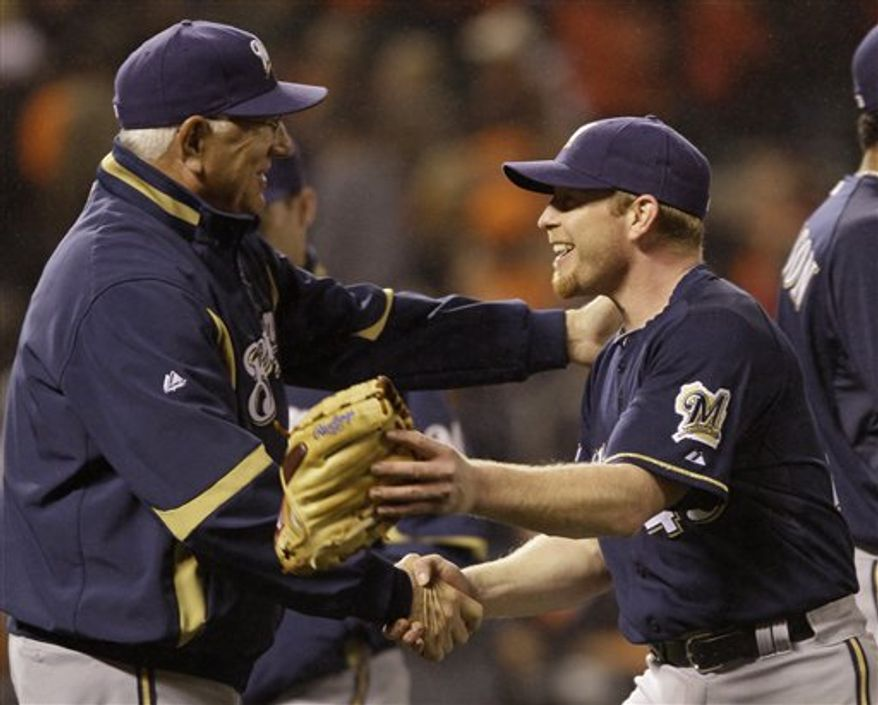 Milwaukee Brewers manager Ken Macha, left, greets starting pitcher Randy Wolf at the end of their baseball game against the San Francisco Giants in San Francisco, Friday, Sept. 17, 2010. Milwaukee won the game 3-0 and Wolf pitched a complete game giving up three hits. (AP Photo/Eric Risberg)
