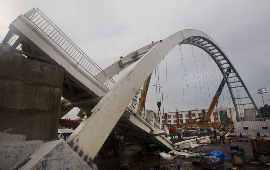 A portion of the collapsed bridge is seen near Jawaharlal Nehru stadium in New Delhi, India, Tuesday, Sept. 21, 2010. The footbridge under construction near the Commonwealth Games main stadium collapsed on Tuesday. The games are scheduled to be held from Oct. 3-14. (AP Photo/Mustafa Quraishi)