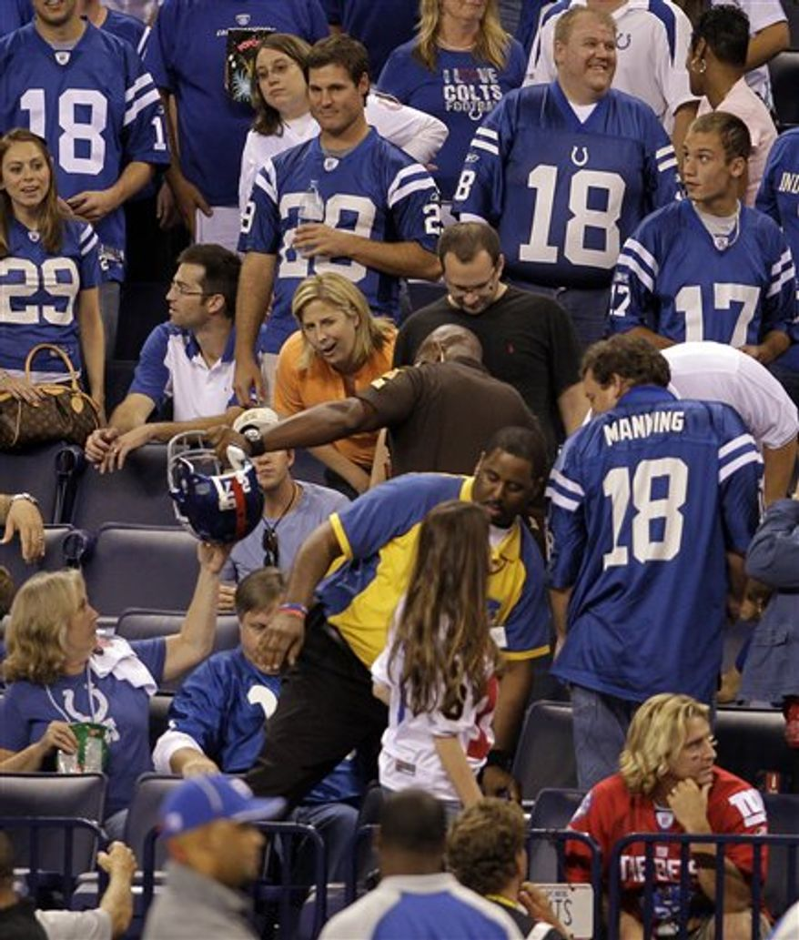 A security officer retrieves the helmet of New York Giants running back Brandon Jacobs from the stands during an NFL football game against the Indianapolis Colts in Indianapolis, Sunday, Sept. 19, 2010. Jacobs apologized for unintentionally throwing his helmet into the stands in the third quarter Sunday night in the Giants' loss to the Indianapolis Colts. (AP Photo/Darron Cummings)
