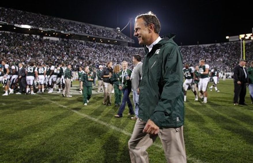 "FILE - In this Sept. 18, 2010 file photo, Michigan State coach Mark Dantonio smiles as he leaves the field following a 34-31 overtime win over Notre Dame in an NCAA college football game in East Lansing, Mich.  Dantonio expects to travel with the team for this weekend's game at Michigan as he recovers from a mild heart attack and subsequent blood clot in his leg.  ""You can't keep me down Michigan week,"" Dantonio said to begin a news conference Tuesday, Oct. 5, 2010. ""It's good to be back _ again."" (AP Photo/Al Goldis, File)"