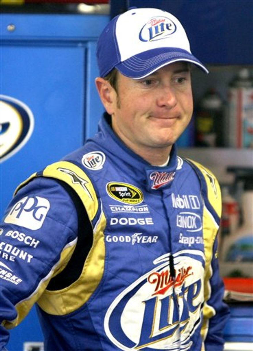 Driver Jimmie Johnson dashes from his hauler to his garage while preparing for practice for the NASCAR Sylvania 300 auto race at the New Hampshire Motor Speedway in Loudon, N.H., Saturday, Sept. 18, 2010. (AP Photo/Charles Krupa)